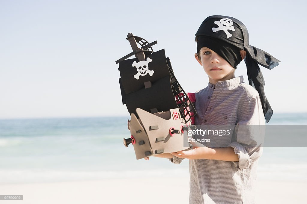 Boy in pirate costume playing with a toy boat : Stock Photo