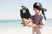 Boy in pirate costume playing with a toy boat