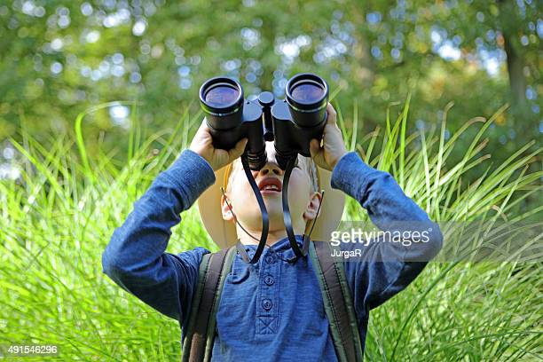 Boy in Pith Helmet Looking Up Through Big Binoculars Outdoors
