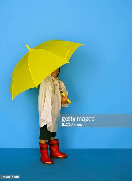 Boy In Raincoat Holding Yellow Umbrella
