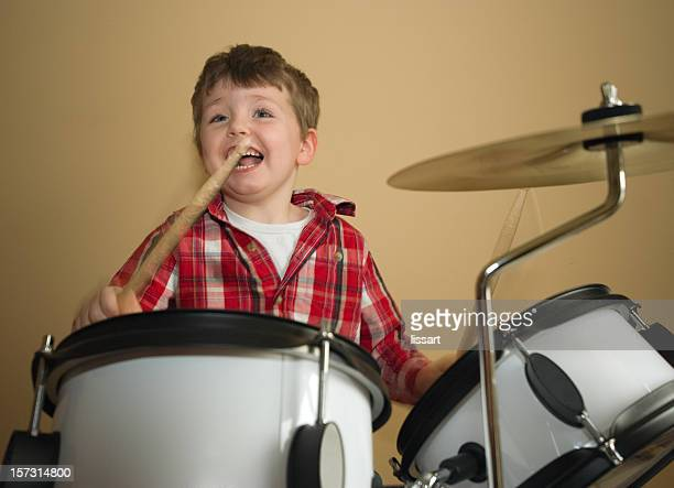 Boy in red checkered shirt happily playing the drums