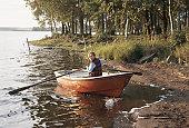 Boy (10-11) in rowing boat, looking over shoulder