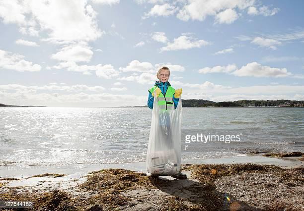 Garçon au gilet de sécurité nettoyage de la plage