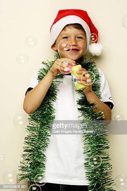 Boy (5-7) in Santa hat blowing bubbles, tinsel around neck, portrait