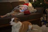 Boy in Santa hat sleeping on sofa