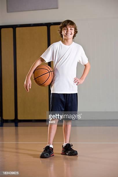 Boy in school gym holding basketball