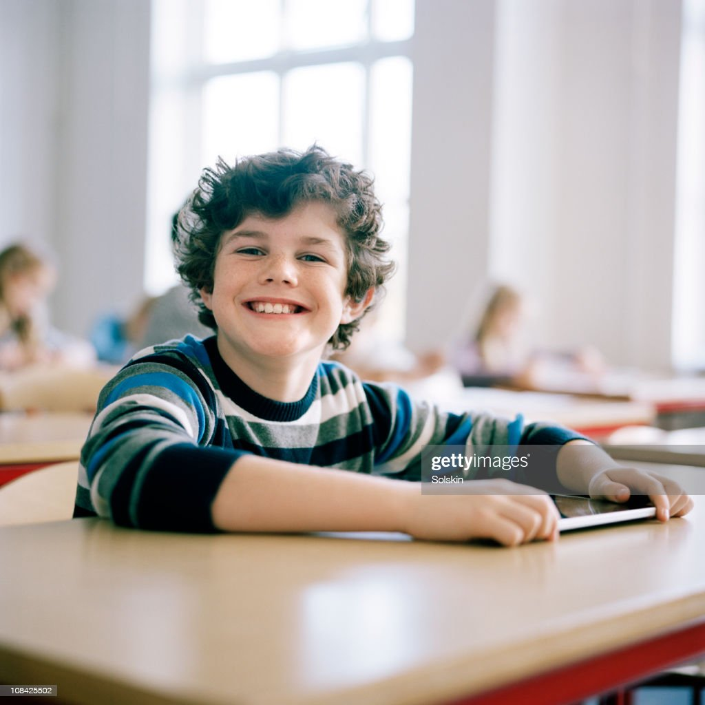 Boy in school, holding portable computer : Stock Photo