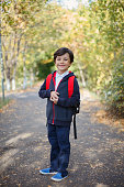 cute boy whose milk teeth fallen, laughing with backpack in park