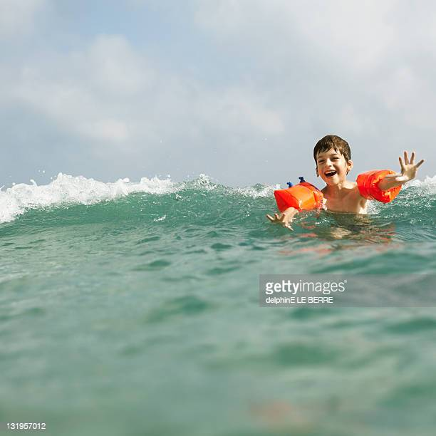 Boy in sea with water wings