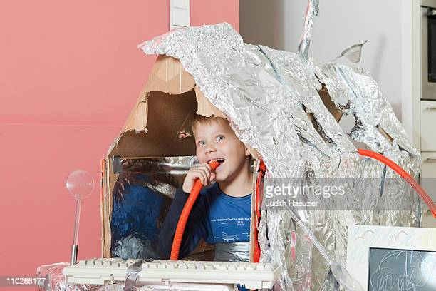 Boy in self constructed house, smiling