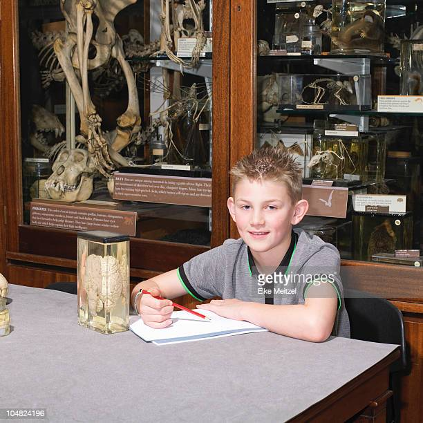 Boy in sitting at table in museum