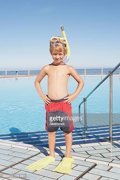 Boy (6-8) in snorkel gear by outdoor pool, hands on hips, portrait
