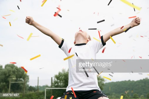 Boy in soccer jersey cheering on soccer pitch