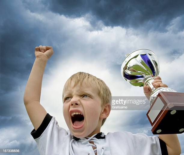 Boy in soccer jersey lifting a trophy of championship