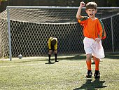 Boy in soccer uniform celebrating, defeated goalkeeper in background (portrait)