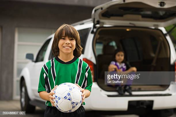 Boy (8-10) in soccer uniform, sister sitting in car