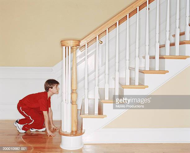 Boy (8-10) in start position at foot of staircase