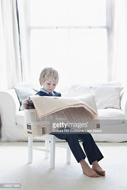 Boy in suit reading newspaper