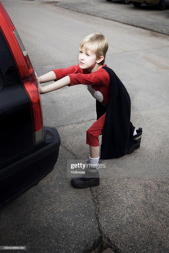 Boy (7-9) in superhero costume pushing car on road, overhead view : Stock Photo