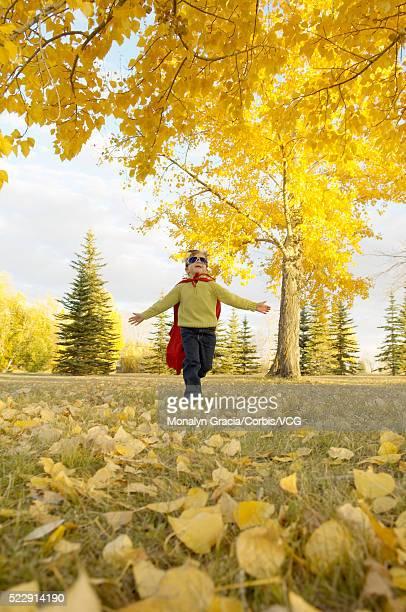 Boy in superhero costume running across field