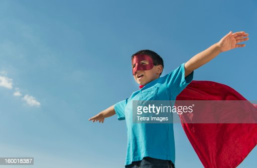 Boy (6-7) in superhero costume under blue sky