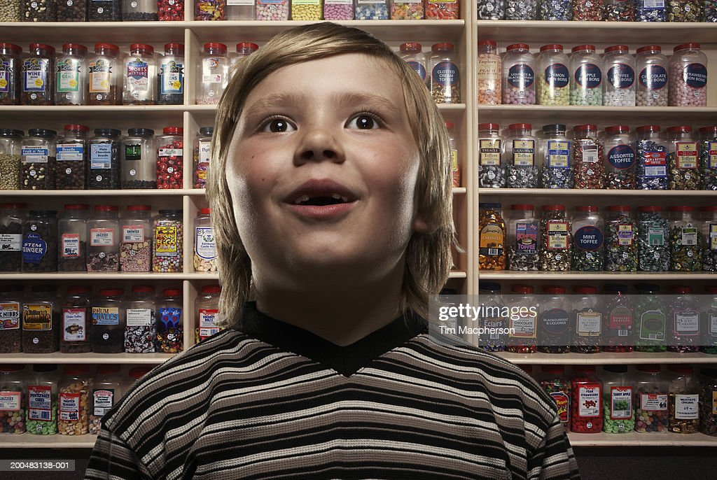 Boy (6-8) in sweetshop, close-up (Digital Composite) : Stock Photo