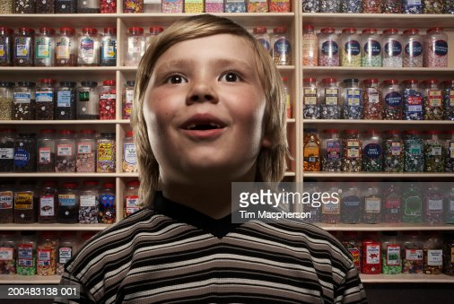 Boy (6-8) in sweetshop, close-up (Digital Composite) : Stock-Foto