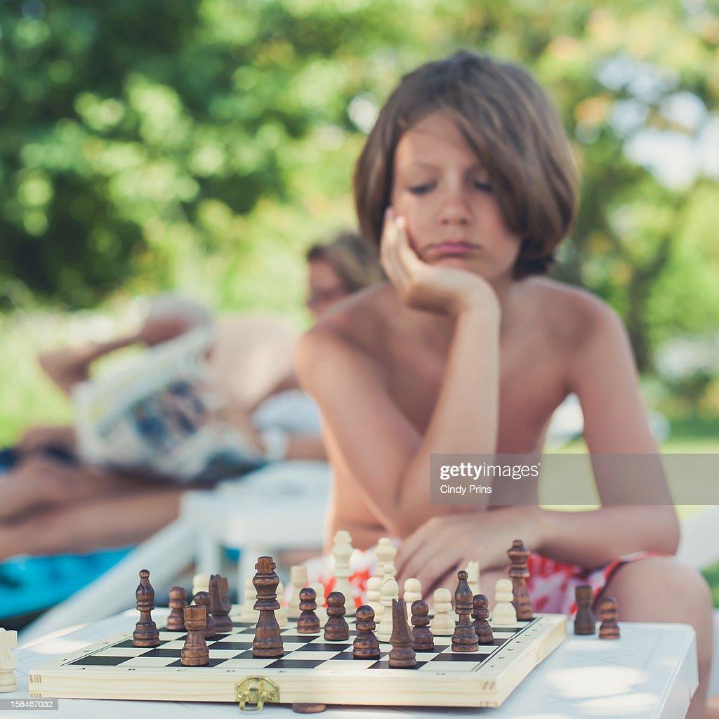 Boy in swim shorts playing chess : Stock Photo