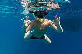 Boy in swimming mask dive in Red sea near yacht, underwater shoot