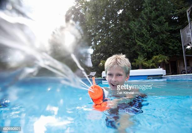 Boy in swimming pool squirting water gun
