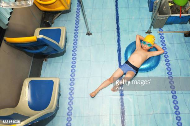 A boy in swimwear poses on a swimming poolthemed bus on August 16 2017 in Jinhua Zhejiang Province of China Bus drivers decorated their bus with blue...