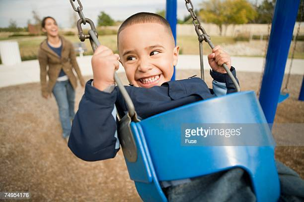 Boy in swing looking back at mom