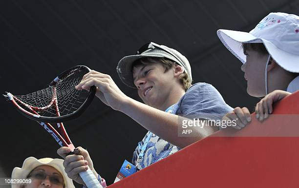 A boy in the crowd holds Stanislas Wawrinka of Switzerland's crushed racquet after Wawrinka smashed it on the ground in reaction to losing a point...