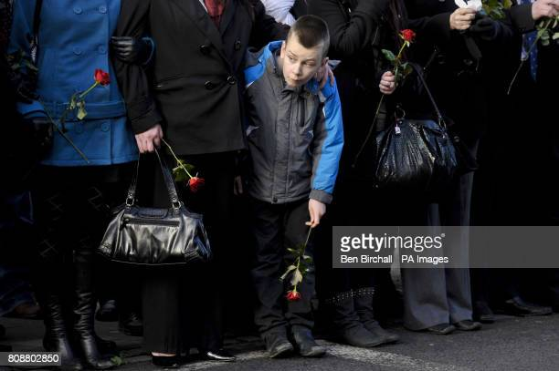 A boy in the crowd on Wootton Bassett High Street holds a single red rose and peeks out to watch as the hearse carrying the coffin of Private Martin...