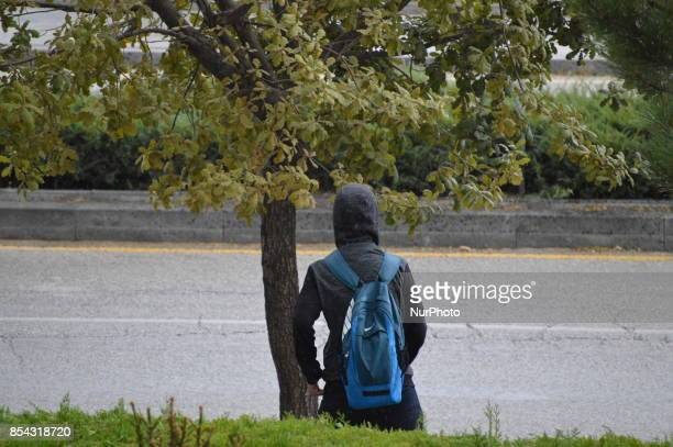 A boy in the hood looks around as he walks next to a rain drenched road during a rainy autumn day in Ankara Turkey on September 26 2017 The...