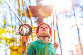 rope course at a summer camp. child wearing a helmet on the obstacle course. blurred background and blurred motion due to the concept