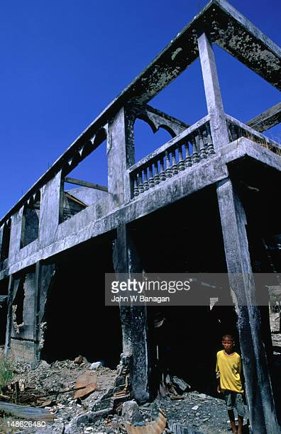 Boy in the shell of a burnt out building, Dili.