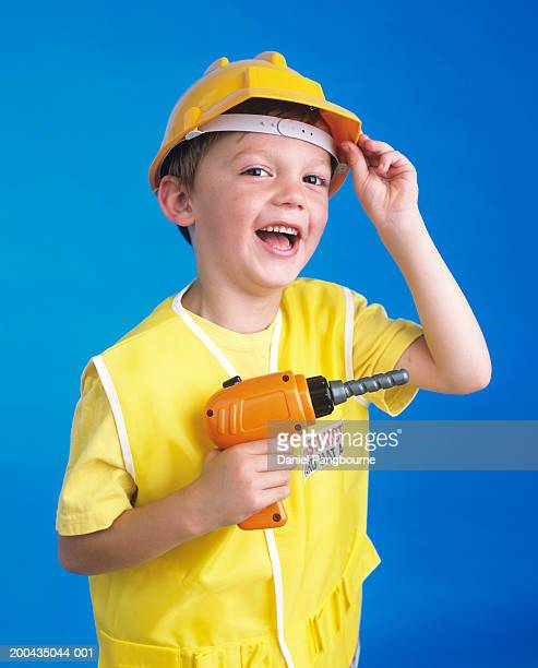 Boy (4-6) in toy hard hat holding toy drill, smiling, portrait