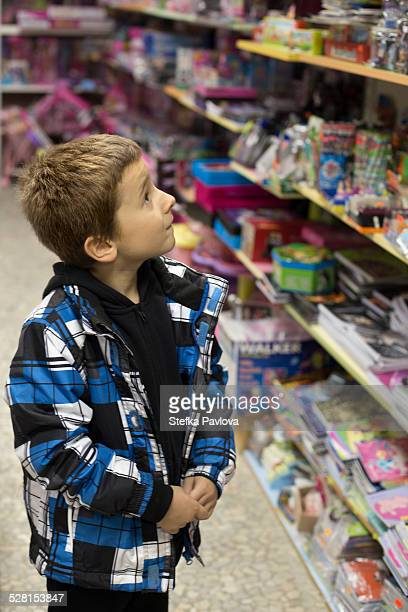 Boy in toy shop feeling confused