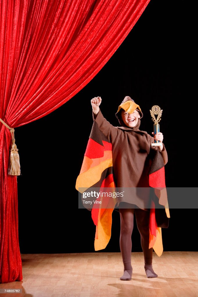 Boy in turkey costume holding trophy : Stock Photo