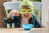 Boy in turtle costume eating cereal