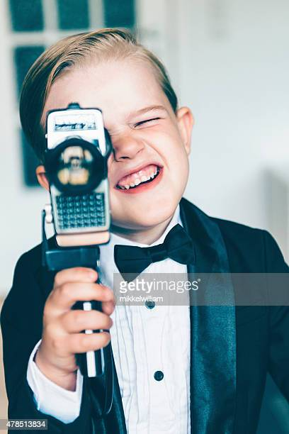 Boy in tuxedo makes movie with old video camera