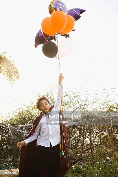 Boy in vampire costume with balloons