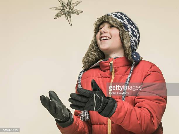 Boy in warm clothes catching star