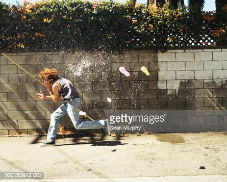 Boy (13-15) in water fight, running from water balloons