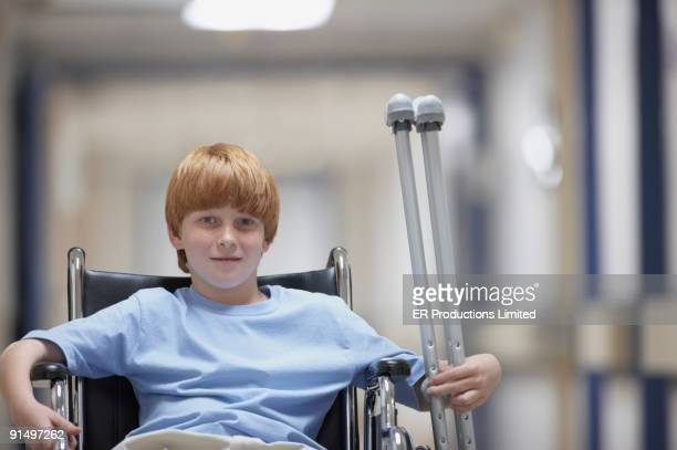 Boy in wheelchair holding crutches