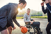 A boy in wheelchair with two teenager friends playing basketball outside at sunset. Close up.