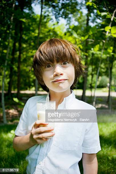 Boy in woods drinking milkshake and pulling a face