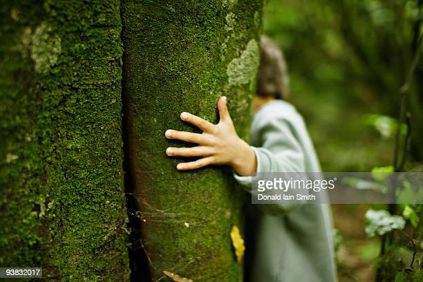 Boy in woods with hand on tree