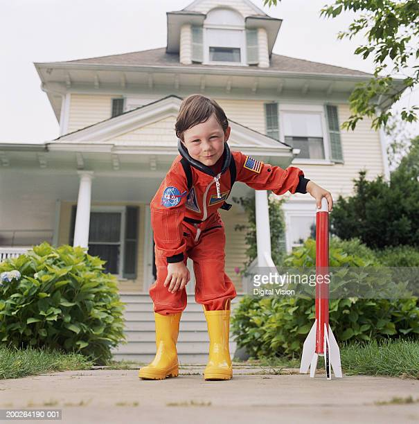 Boy (3-5) in yellow wellington boots, hand on toy rocket, portrait
